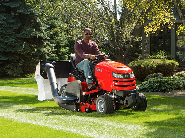 Man mowing lawn with Simplicity lawn tractor that has a dual bag collection system