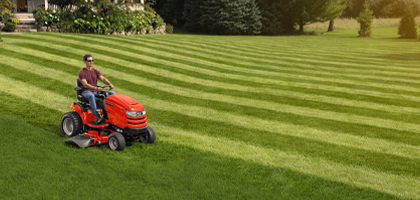 Man riding Simplicity tractor on striped lawn