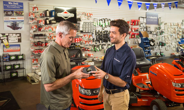 Simplicity dealer showing a lawn mower part to a customer